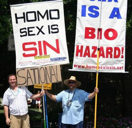 Paranoid men holding Homo Sex Is Sin sign