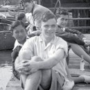 A black and white photograph of a young Alan Turing with 5 of his peers. He is sat with his friends on a wooden dock in the sunshine, his sleeves on his shirt are rolled up and he wears shorts. In the background there is a collection of wooden boats moored at the dockside and some ashore.